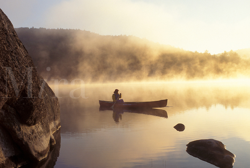 canoeing, canoe, Vermont, VT, Woman paddles a canoe on Kettle Pond in the mist in Groton State Forest.