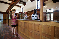 NWA Democrat-Gazette/DAVID GOTTSCHALK  Joi Knight (from left), director of development with Haas Hall Academy, David Swain, project manager, and Stacy Keenan, director of development, speak Tuesday, July 25, 2017, in the restored lobby area at the new Haas Hall Academy Rogers Campus in Rogers. The campus is in the former historic Lane Hotel in the Rogers Commercial Historic District.