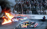 NASCAR driver Tony Raines crouches next to the wall behind his burning race car after crashing with Hank Parker Jr. during a Busch Series race at Richmond, VA on Friday, 9/8/00.  (Photo by Brian Cleary)