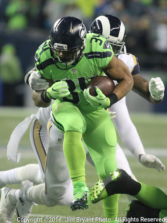 Seattle Seahawks running back Thomas Rawls (34) is wrapped up by Los Angeles Rams Los Angeles Rams middle linebacker Alec Ogletree (52) after gaining 4-yards at CenturyLink Field in Seattle, Washington on December 15, 2016.  The Seahawks beat the Rams 24-3.  ©2016. Jim Bryant Photo. All Rights Reserved