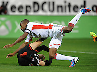 Washington, D.C.- March 29, 2014. Fabian Espindola (9) of D.C. United gets fouled by Jose Goncalves (23) of the New England Revolution.  D.C. United defeated the New England Revolution 2-0 during a Major League Soccer Match for the 2014 season at RFK Stadium.