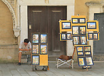 Artist and street vendor using smart phone, Venice, Italy.