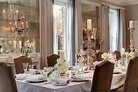 The dining room is furnished with a long refectory table by Rupert Bevan and is decorated for Christmas