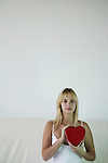 Young woman holding a heart shaped box