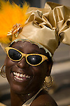 A woman laughs while dancing in the street parade for the ZomerCarnaval (Summer Carnival) in Rotterdam, the Netherlands. The street parade is the colorful high point of the Rotterdam carnival. It is a tropical themed parade with over 2000 participants and travels 6km through the center of Rotterdam.