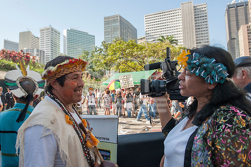An indigenous woman camera operator films an interview with a tribal leader at the protest outside BNDES, the Brazilian National Development Bank, following a march from the People's Summit at the United Nations Conference on Sustainable Development (Rio+20), Rio de Janeiro, Brazil, 18th June 2012. Photo © Sue Cunningham.