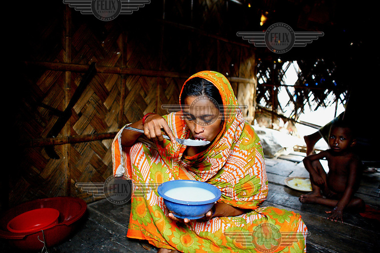 A woman tastes some food that she has cooked in her home in one of the city's slum districts. It is thought that more than six million people live in slums in Dhaka.