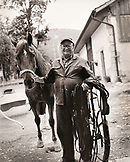 SWITZERLAND, Motiers, Lutin stands with his horse Clatiola after training, Jura Region (B&W)