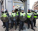 """© Joel Goodman - 07973 332324 . 26/03/2011 . London , UK . Police protect the entrance to a branch of HSBC in Cambridge Circus after a black bloc of protesters carrying black and red anarcho-syndiclist flags use a wheelie bin to smash through the doorway and spray graffiti on the walls . Hundreds of thousands of people attending an anti cuts demonstration under the banner """" March for the Alternative """" in central London , in protest at the coalition government's austerity measures . Photo credit : Joel Goodman"""