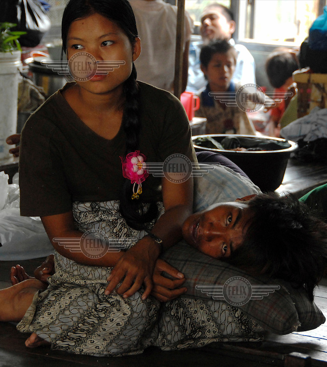 A couple shelter in the secondary school that has been given over to those displaced by Cyclone Nargis, which struck Burma on 02/05/2008. Myad Taw Lane, 2 ward, North Okkala.