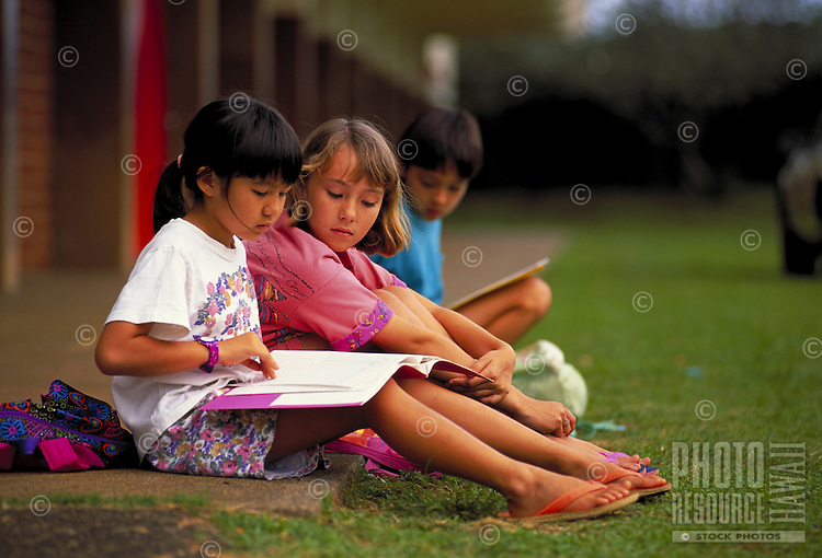 Children read books together on the grass outside their school.