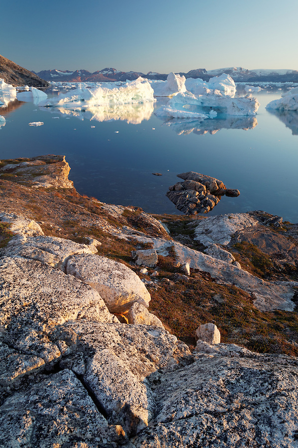 Icebergs and bedrock at dusk along Sermilik Fjord near settlement of Tiniteqilaq, East Greenland