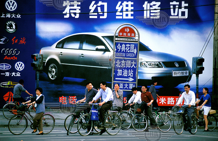 Mark Henley/Panos Pictures..China, Beijing..Contrast: Car advertising and cyclists.