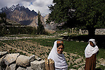 Hunaz woman in the village of Kamaris with the imposing peaks of the mountain known as The Cathedral in the background.