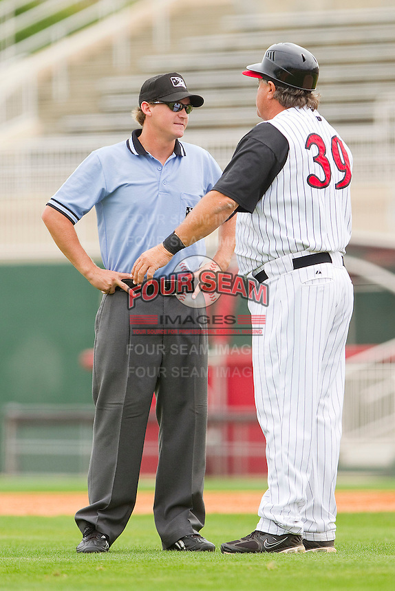 Base umpire Ryan Clark listens closely as Kannapolis Intimidators manager Tommy Thompson #39 argues a call during the South Atlantic League game against the West Virginia Power at Fieldcrest Cannon Stadium on April 20, 2011 in Kannapolis, North Carolina.   Photo by Brian Westerholt / Four Seam Images