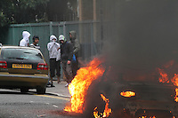 A group of youths stand near a car on fire, destroyed during a riot in the London borough of Hackney. London saw the beginnings of riots on Saturday evening, after a peaceful protest in response to the shooting by police of Mark Duggan during an attempted arrest, escalated into violence. By the third night of violence, rioting and looting had spread to many areas of the capital and to other cities around the country.