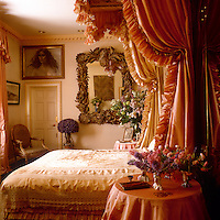 Pinked ruches edge the hangings  and curtain pelmet on this bed, details which echo the elaborate ornamental carving of the mirror on the wall