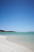 A deserted white sandy beach and blue sea