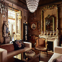 A traditional sitting room with gilt mirror frames hanging above an ornate fireplace. Two modern sofas in neutral upholstery and an antique armchair are set around a coffee table with a mirror top. A pair of French doors leads to a room beyond.