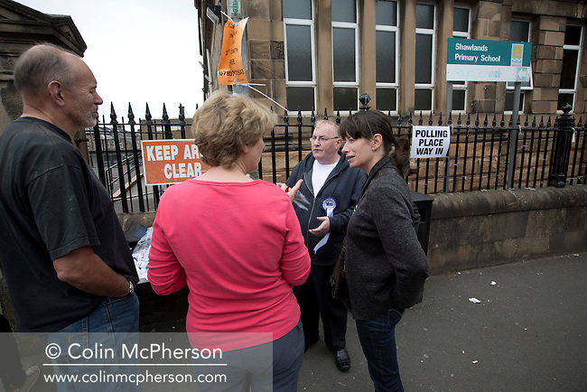 Pro-independence activists talk to voters outside a polling station in Shawlands, Glasgow on the day of the independence referendum. Yes Scotland were campaigning for the country to leave the United Kingdom, whilst Better Together were campaigning for Scotland to remain in the UK. On the 18th of September 2014, the people of Scotland voted in a referendum to decide whether the country's union with England should continue or Scotland should become an independent nation once again and leave the United Kingdom.