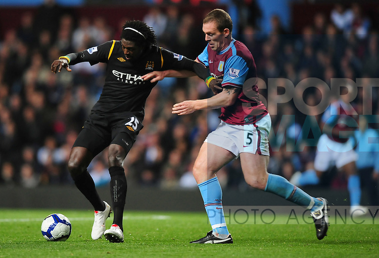Emmanuel Adebayor of Manchester City holds off Richard Dunne of Aston Villa