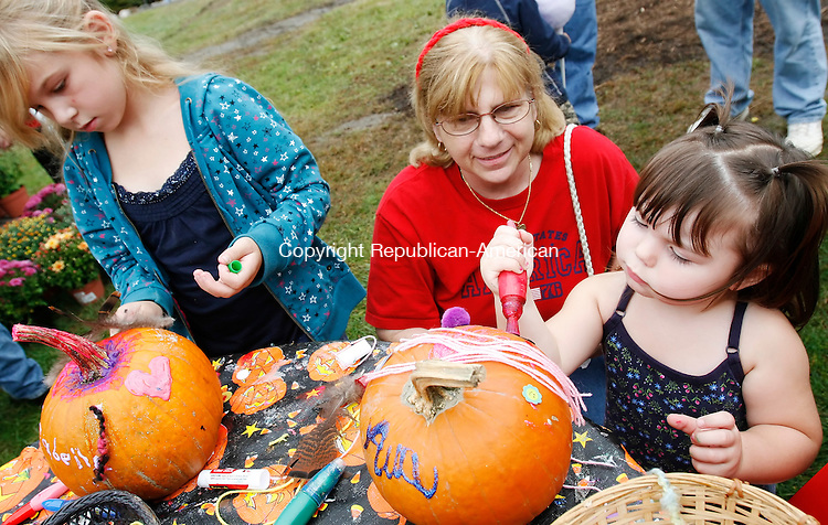 MIDDLEBURY, CT, 09/28/08- 092808BZ04- Judy Roque, of Carmel, NY, center, watches as her granddaughters Annabella Hare, 7, left, and Ava Hare, 2, of Middlebury, decorate pumpkins at the St. John of the Cross Apple Harvest festival at the Shepardson Community Center Sunday afternoon.<br /> Jamison C. Bazinet Republican-American