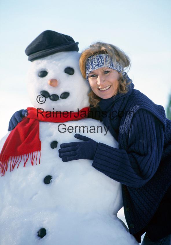 Deutschland, Bayern, Chiemgau: junge Frau umarmt laechelnd einen Schneemann | Germany, Bavaria, Chiemgau region: young woman smiling, embraces a snowman