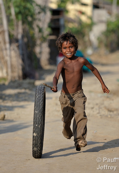 A boy at play, rolling an old tire through the dusty streets of Irula, a small village in southern India's state of Tamil Nadu.