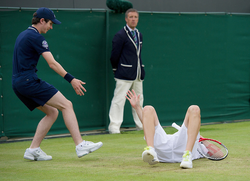 Mardy Fish (USA)[10] calls for help from a ball boy after taking a tumble during his defeat by Jo-Wilfried Tsonga (FRA)[5] in their Gentlemen's Singles Fourth Round match - Jo-Wilfried Tsonga (FRA)[5] def Mardy Fish (USA)[10]..Tennis - Wimbledon Lawn Tennis Championships - Day 8 - Tuesday 3rd July 2012 -  All England Lawn Tennis and Croquet Club - Wimbledon - London - England...