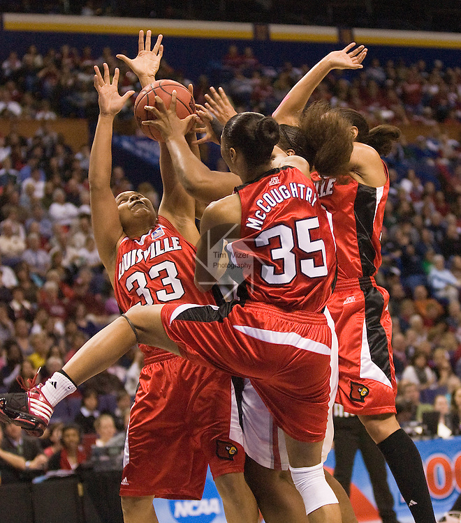 040509TVFINALFOUR6.Louisville players (from left) Monique Reed (33), Angel McCoughtry (35) and Candyce Bingham (13, partially hidden) surround Oklahoma's Courtney Paris (3, mostly hidden in center) under the bucket in first half action at the first semifinal of the NCAA Women's Final Four championship at the Scottrade Center in St. Louis, MO on Sunday April 5, 2009..MCT/TIM VIZER