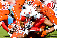 January 1, 2009:      Nebraska running back Roy Helu Jr. (10) is tackled as Clemson's Da'Quan Bowers tries to strip the ball from his hands during the 64th annual Konica Minolta Gator Bowl between the Nebraska Cornhuskers  and the Clemson Tigers  at Jacksonville Municipal Stadium in Jacksonville, Florida. Nebraska defeated Clemson 26-21.