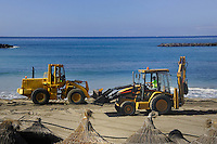 Yellow tractors cleaning up beach, Playa de las Americas,Tenerife, Canary Islands
