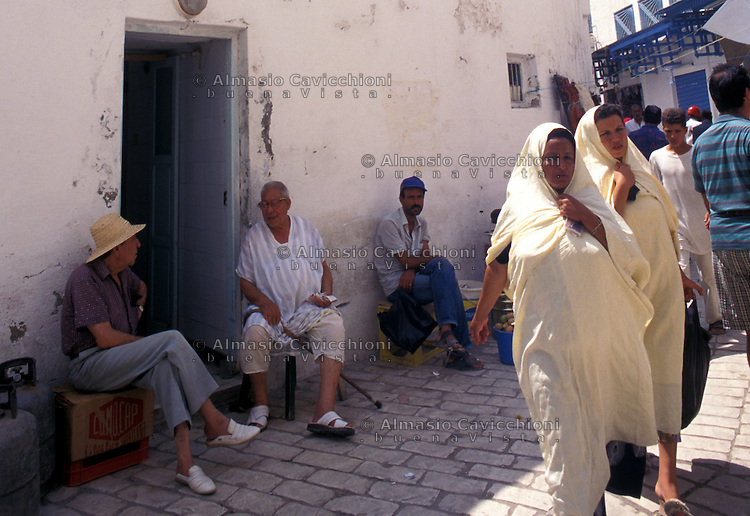 Tunisia, citt&agrave; di Kairouan, donne e uomini in abiti tradizionali in una strada della Medina.<br /> Tunisia, the city of Kairouan, women and men in traditional clothes in a street in the Medina.