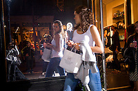 A shopper outside the Cynthia Rowley boutique on Bleecker Street in the West Village in New York on Friday, September 10, 2010 during the second annual Fashion's Night Out event. On the first evening of New York Fashion Week stores around the city offered sales and bargains as well as parties and events to entice customers to shop. The event has been so successful in boosting sales that this year over 100 cities in the US are having their own events, and Fashion's Night Out is being planned for 16 countries. (© Frances M. Roberts)