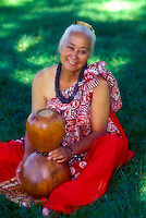 Hawaiian woman wearing kukui nut necklace seated with ipuheke gourd used for dancing hula