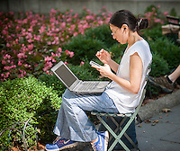 A woman uses her laptop and smartphone in Bryant Park in New York on Friday, August 21, 2015. (© Richard B. Levine)