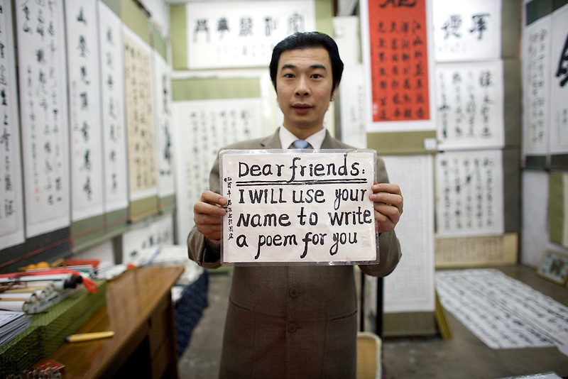 The owner of a calligraphy shop offers tourists a deal, written in English, to use their name to write Chinese poetry in the village of Zhouzhuang in Jiangsu Province.