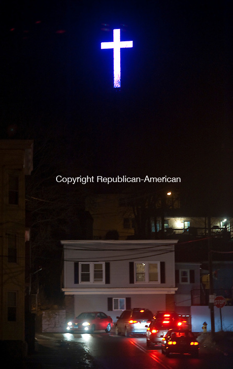 WATERBURY, CT-122213JS05-Traffic makes its way up and down East Liberty Street as the cross on Pine Hill at Holy Land again shines over the city of Waterbury following a lighting ceremony on Sunday. <br /> Jim Shannon Republican-American