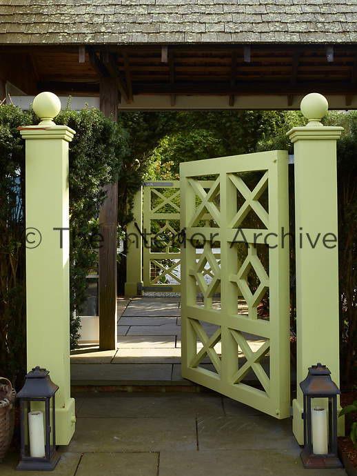 A painted gate leads into the courtyard garden. Two hurricane lamps stand either side of the gate.