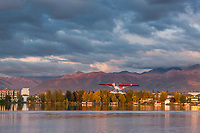 Rusts flying service bush plane taxis along Lake Hood, Anchorage, Alaska, Chugach mountains in the distance.