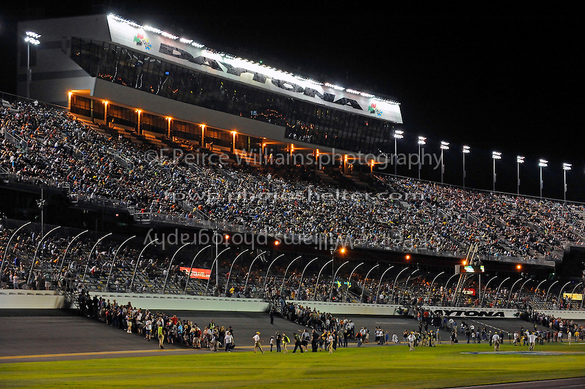 "Fans stream off the ""ballfield"" and into the stands for the truck race."