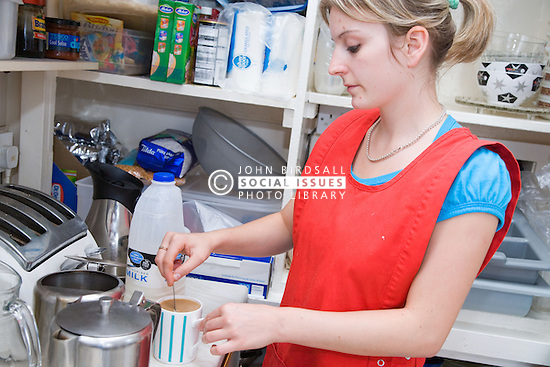 Young cook taking a break from work and making a cup of tea in kitchen of Polish Social Club,