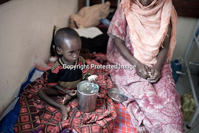 WAJIR, KENYA - JULY 6: Dahaba Hassa, age 60, with her grandchild Abukar Abadi, age two, eat rice after being admitted to the stabilization center in Wajir on July 6 in central Wajir, Kenya. The child was referred to the stabilization center in Wajir by Save the Children. Two successive poor rains, entrenched poverty and lack of investment in affected areas have pushed millions of people into a fight for survival in the Horn of Africa. This is the driest this area has been since sixty years. People in smaller town are usually fortunate to have water. In rural areas, most wells has dried up and some people was as much as eight kilometers to fetch water. Most of the livestock has perished and the remaining stock has often been taken far away for better conditions. Many has even crossed into neighboring Somalia for better pasture. (Photo by Per-Anders Pettersson)