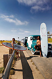 USA, California, San Diego, Aaron Scott rests holding his surfboard on the hood of his car