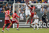 Omar Gonzalez defender of the LA Galaxy leaps to battle with FC Dallas midfielder Atiba Harris. The LA Galaxy defeated FC Dallas 2-1 at Home Depot Center stadium in Carson, California on Sunday October 24, 2010.