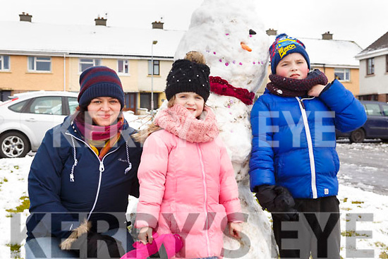 Samantha Fitzgerald with her children, Jessica and Brandon O'Connor braving the elements in Shanakill on Friday morning last.