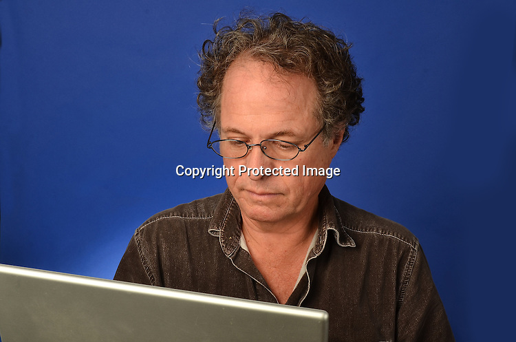 Old man on computer stock photo