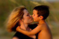 A mother kisses her young son in the glow of the evening sun as the wind blows her hair. Photo taken at the beach with sand dunes and sea grass blowing behind them.