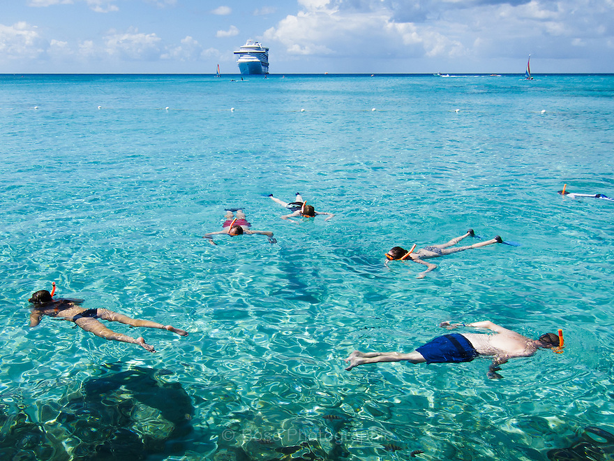 Six youths snorkeling with sailboats and cruise ship behind, Princess Cays, Eleuthera, Bahamas
