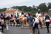 The procession riding towards the old town of Prague with spectators following.<br /> The Ride of the Kings takes place during the spring, as a part of the Pentecost traditions, in the towns of Hluk and Kunovice and the villages of Skoronice and Vlčnov. A group of young men ride through a Prague in a ceremonial procession. The ride is headed by chanters, followed by pageboys with unsheathed sabres who guard the King &ndash; a young boy with his face partially covered, holding a rose in his mouth &ndash; and the rest of the royal cavalcade. The King and pageboys are dressed in women&rsquo;s ceremonial costumes, while the other riders are dressed as men. The entourage rides on decorated horses, stopping to chant short rhymes that comment humorously on the character and conduct of spectators. The chanters receive donations for their performance, placed either in a money box or directly into the riders&rsquo; boots. The King&rsquo;s retinue returns home after a few hours of riding, and celebrates in the evening at the house of the King with a small feast, music and dancing. The practices and responsibilities of the Ride of the Kings are transmitted from generation to generation. The traditional paper decorations for the horses and the ceremonial costumes, in particular, are made by women and girls familiar with the processes, colour patterns and shapes specific to each village.